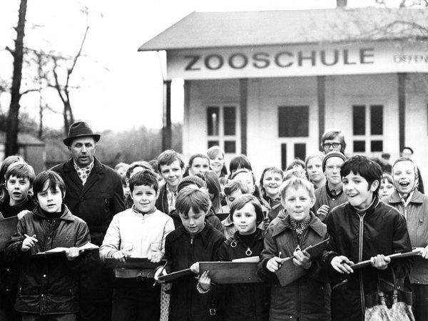 Zooschullehrer Heinz Mohr mit einer Schulklasse auf dem Reitplatz vor der Zooschule bei der Beobachtung von Menschenaffen, Foto: Zoo Archiv um 1970