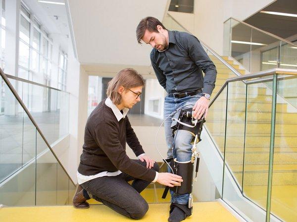 Felix Weiske (links) und Max Böhme beim Testen des Exoskeletts in der HTWK Leipzig, Foto: HTWK Leipzig
