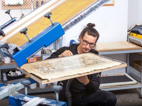 Dennis Blumenstein bei der aufwändigen Herstellung der Replik des Papyrus Ebers per Siebdruckverfahren in der Leipziger Werkstatt von Schmidt, Blumenstein GbR, Foto: Universität Leipzig / Swen Reichhold