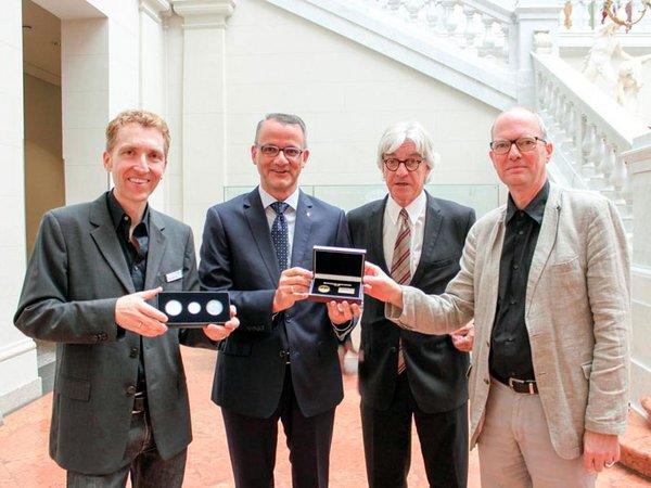 """Degussa überreicht dem Münzkabinett der Universitätsbibliothek Leipzig neue Gedenkmedaille """"1000 Jahre Leipzig"""" in Gold und Silber"""