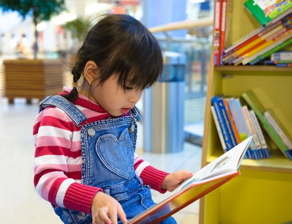 Ein kleines Mädchen schaut ein Buch an.